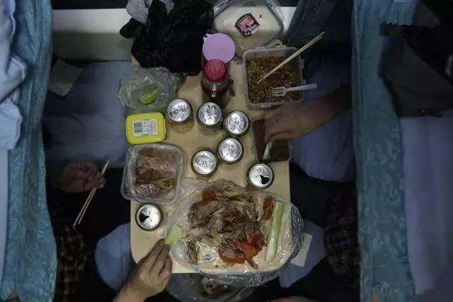 """但凡坐过火车的人,想必都对这句叫卖声耳熟能详:""""啤酒饮料矿泉水,瓜子花生八宝粥,来,腿让一让啊!""""坐火车久了无聊,买点儿零食垫垫肚子,消磨时间。这些弥散的食物之味,渐渐汇聚成我们印象中春运的味道。(图片来自腾讯网、新华网、东方网))"""