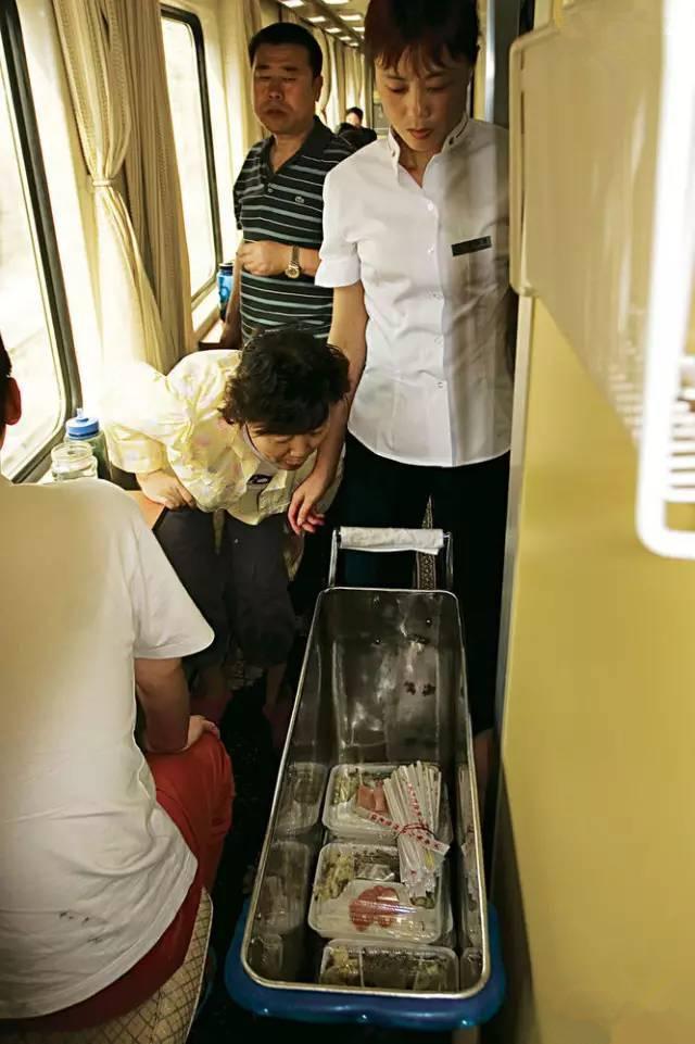 其实,现在每列火车上都专门有一间餐车车厢,供长途出行的旅客吃饭。但春运前后,这里却往往沦为大量买不着票的旅客的栖身之所,要吃饭的旅客只能从推着小车穿行来往的服务员那里购买。图为甘肃兰州,服务员在青藏铁路的列车上卖盒饭。(图片来自腾讯网、新华网、东方网)