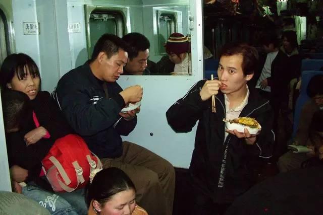 2005年春运期间,广州开往长沙的列车上,旅客在车厢走廊上吃盒饭。(图片来自腾讯网、新华网、东方网)