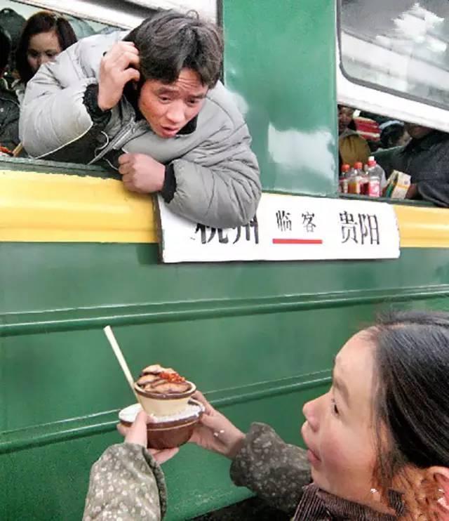 2005年春运期间,杭州首趟民工列车投入运营,一位旅客看着车站小贩手中的饭菜考虑要不要买。(图片来自腾讯网、新华网、东方网)
