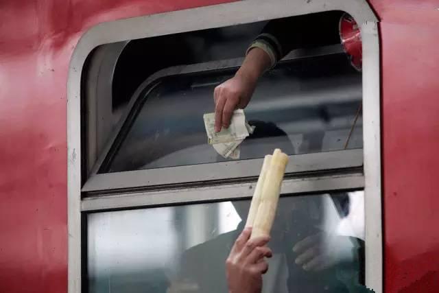 2011年春运期间,湖北襄阳火车站,已经登车的旅客从车窗伸手递钱购买甘蔗。(图片来自腾讯网、新华网、东方网)
