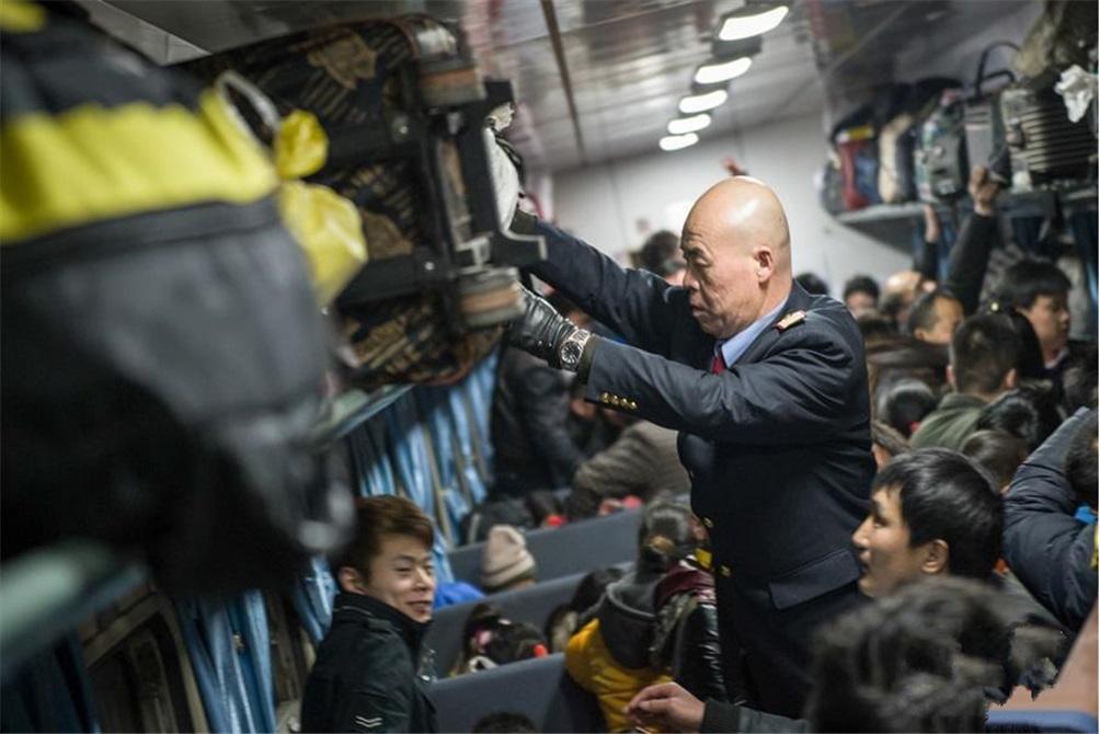 2014年1月21日深夜,上海开往阜阳的L8572次临客绿皮列车上乘务员潘珉帮刚上车的旅客整理行李。(图片来自新华网)