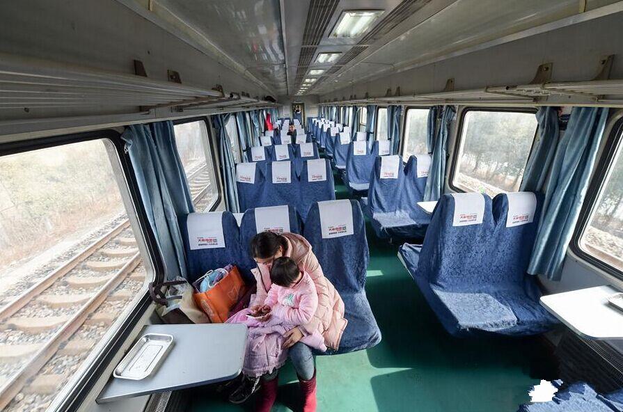 """2月4日,在安徽阜陽開往上海的K8365次列車上,一名旅客與孩子在玩手機。當日,記者登上從安徽阜陽開往上海的K8365次列車發現,硬座及軟臥共有403名旅客,該列車定員1175人,部分車廂整節空置。據了解,安徽阜陽是勞動力輸出大市,在外務工人員較多,春節前阜陽火車站以返鄉客流為主,""""逆向出行""""旅客少。新華社記者 張端 攝"""