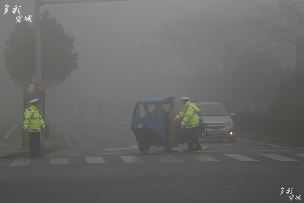 雾中安全守护神(1月3日上午,郎溪被雾霾笼罩,部分区域能见度不到20米,郎溪交警全警上路,确保道路交通安全。)陈家来摄