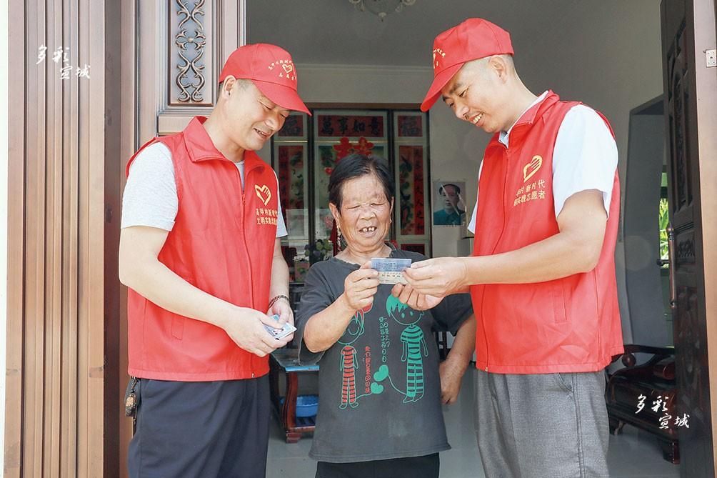旌德县城乡公交一体化于7月1日正式运营,凭老年证可享受乘车优惠。白地镇高甲村的志愿服务队员急老人所急,义务为全村265位老人办理好老年证,并送到老人们的手上,得到村民的点赞。图为志愿者将老年证送到76岁的高小女手上时,老人家脸上乐开了花。  特约记者 江建兴 摄
