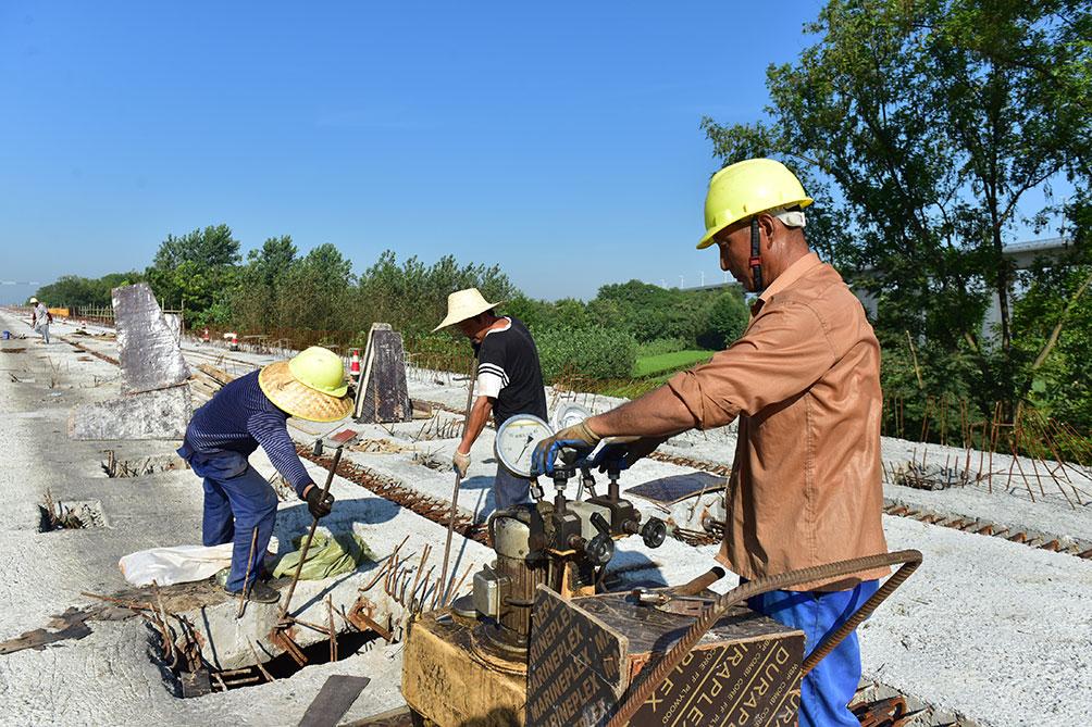 宣城市青弋江大道七标工程为新建城市I级主干道,道路西接环城大道上跨皖赣铁路桥,向东上跨水阳江,经芜屯路至陵阳路,全长2944.345米,工程造价3.76亿元。目前正在进行桥面附属结构施工,预制梁架设已完成97%。整个工程预计2019年11月30日全线完工,该工程的完工之日也就是我市三环道路的全线贯通之时。图为工人们正顶着烈日加紧施工。  记者 戴巍 摄