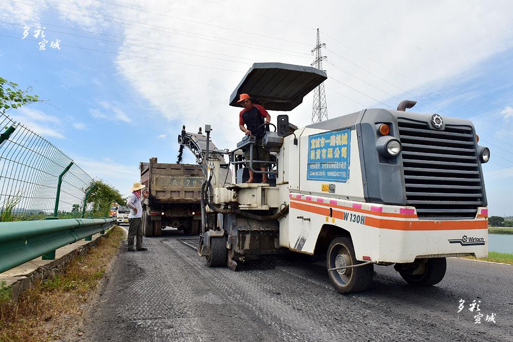 图为8月8日上午,公路局施工队正头顶烈日在公路上进行挖补(铣刨)、沥青混凝土罩面的应急养护作业。 陈丹 记者 戴巍 摄