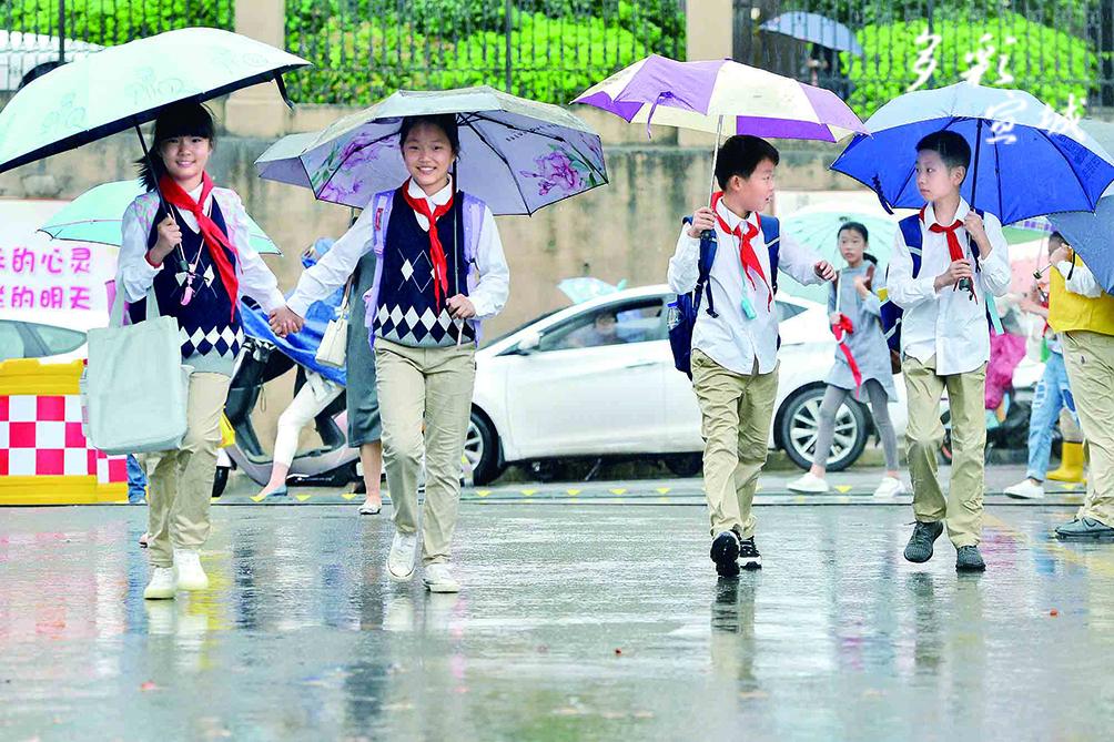 9月2日,全市中小学开学。市十一小学校门口,度过了暑假的小学生们相伴回到校园,虽然天空飘着大雨,但孩子们的脸上写满了开心。记者 汪辉 摄