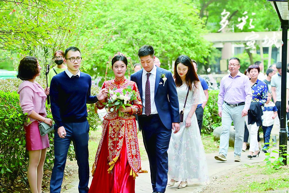 國慶節期間,市區一小區內,一對新婚小夫妻在家人的簇擁下,步行串街走巷,完成接親等婚禮流程。據了解,這種沒有豪華車隊,沒有鞭炮禮花的喧鬧,時尚而簡約的低碳婚禮,已成為我市越來越多年輕新人倡導的結婚新風尚。記者 汪輝 攝