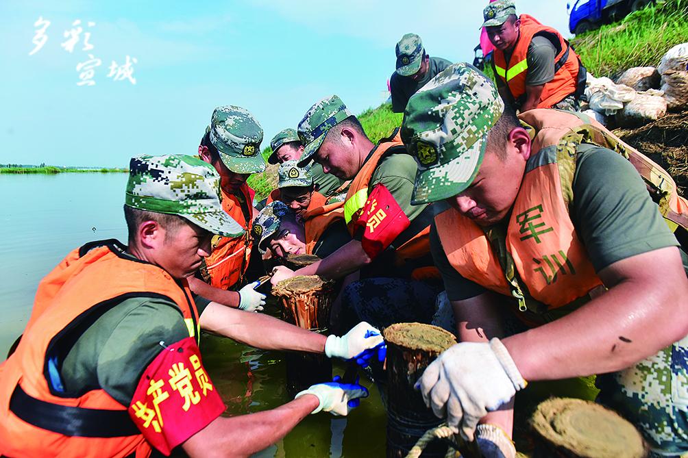 7月25日8時,郎溪縣躍進圩前期加固段出現蟻穴涌漏險情,第72集團軍某旅突擊車連迅速出動,作業約2小時,投入200袋砂石,緊急加固搶筑堤埂。對堤埂7-8段出現的兩處管涌,該連隊查明情況后與地方專家商議對策,決定成立17人的黨員突擊隊下水打樁。突擊隊水中作業近8小時,打樁27根,拋填砂石料千袋約35噸,妥善處置了險情、加固了堤埂。