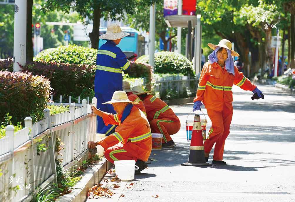为营造更加整洁的城市环境,大街小巷处处都有环卫工人忙碌的身影,他们用辛苦的劳动提升城市的颜值。图为环卫工人们正在清洁路边绿化带栅栏。 全媒体记者 叶竞文 摄