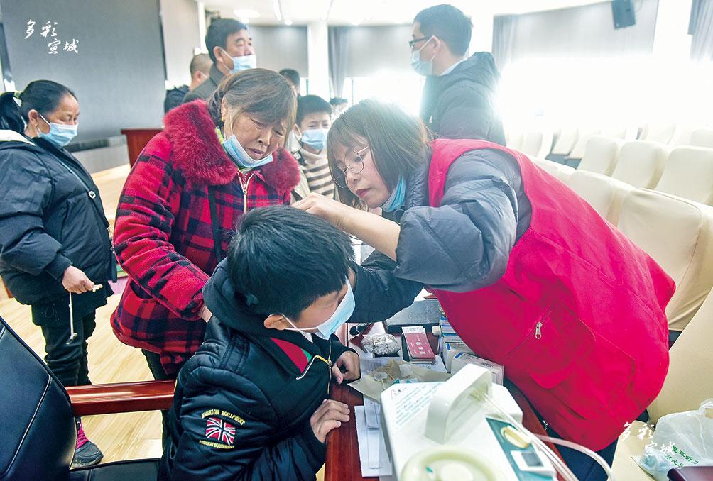 """3月3日是全国第22个""""爱耳日"""",主题为""""人人享有听力健康""""。3月2日上午,由宣州区残疾人联合会主办的第22个""""爱耳日""""宣传教育活动,在宣城市特殊教育中心报告厅举行。现场,宣城市中医院耳鼻喉科专家作了相关科普知识讲座,服务人员为听力障碍儿童提供助听器、人工耳蜗保养。 全媒体记者 戴巍 摄"""